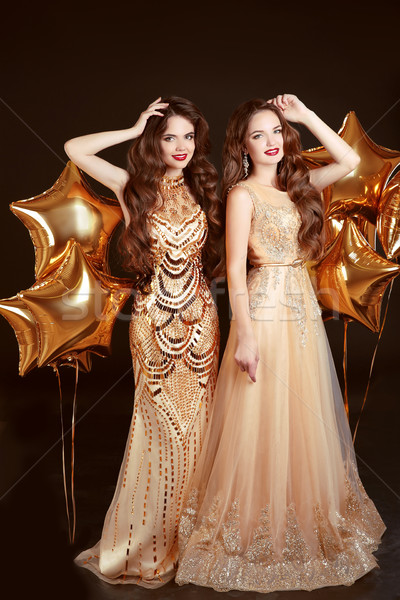 Two women in fashion dress, party celebration. Brunette twins gi Stock photo © Victoria_Andreas