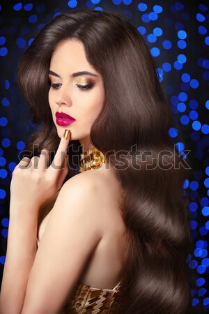 Beautiful elegant model brunette with long wavy hair and jewelry Stock photo © Victoria_Andreas