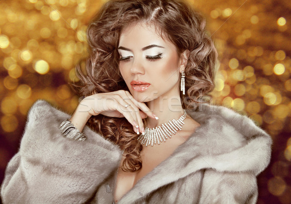 Luxury fashion beauty woman in fur coat over golden bokeh backgr Stock photo © Victoria_Andreas