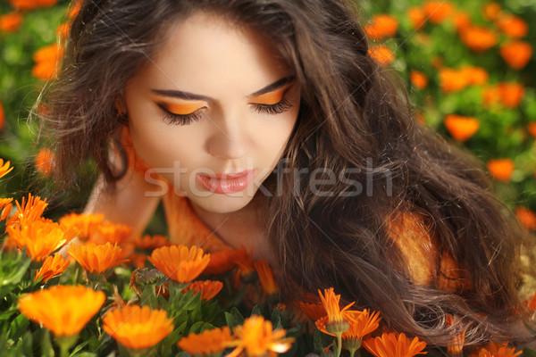 Beauty portrait. Eye Makeup. Beauty Girl over marigold flowers f Stock photo © Victoria_Andreas
