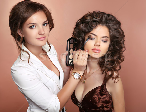 Curly hair. Beauty makeup. Professional artist woman applying ma Stock photo © Victoria_Andreas
