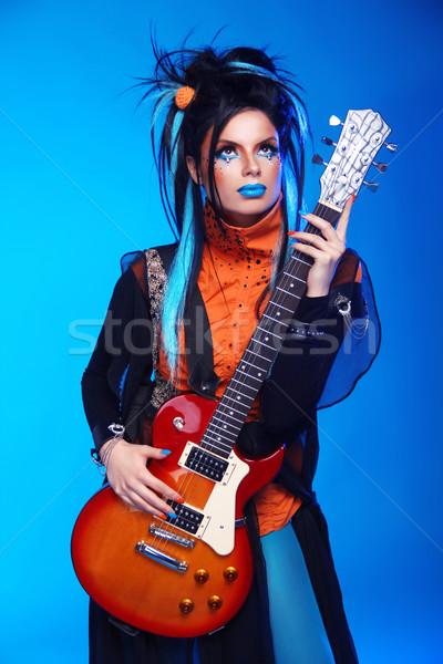 Punk rock girl guitarist posing over blue studio background. Tre Stock photo © Victoria_Andreas