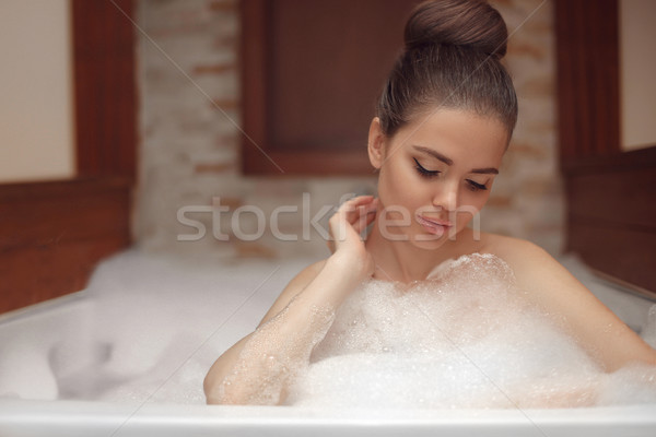 Young woman relaxing in foam jacuzzi bath spa, brunette enjoying Stock photo © Victoria_Andreas