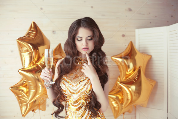 party celebration, gorgeous young woman in golden dress thinking Stock photo © Victoria_Andreas