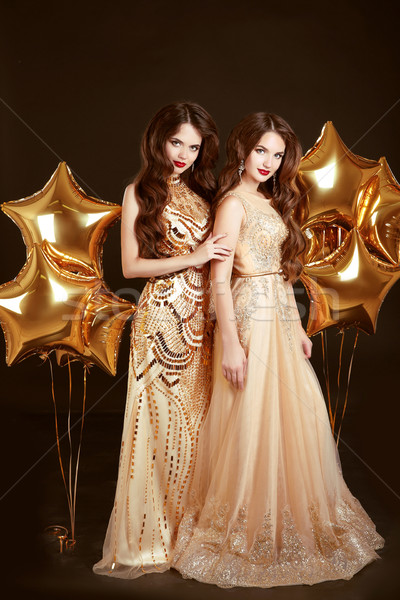 Elegant ladies on party. Beautiful sexy girls wearing in gold fa Stock photo © Victoria_Andreas