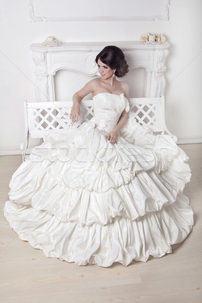 Beautiful bride woman sitting on luxuriant wedding dress over wh Stock photo © Victoria_Andreas