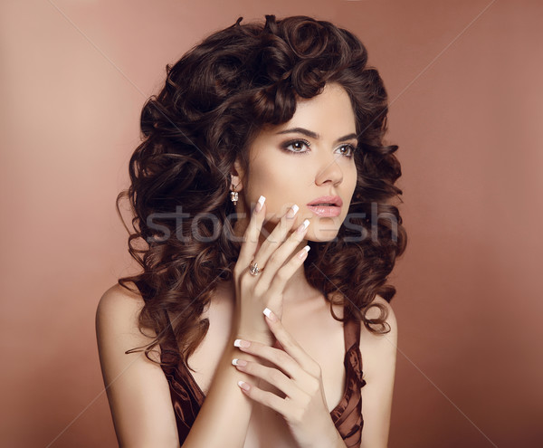 Beautiful girl with long curly hair. Makeup. Manicured nails. Br Stock photo © Victoria_Andreas