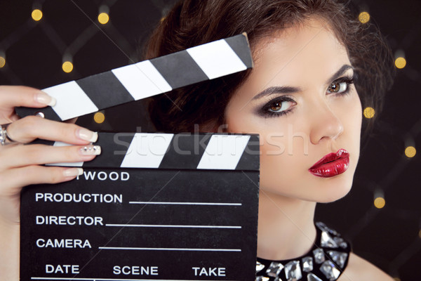 Fashion elegant woman with sexy red lips holding cinema clap. Su Stock photo © Victoria_Andreas