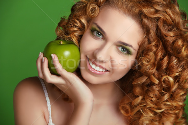Young happy smiling beautiful woman with apple. Curly hair Stock photo © Victoria_Andreas