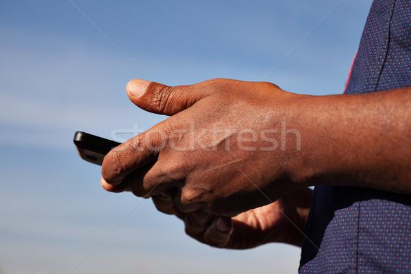 Zwarte handen telefoon blauwe hemel achter Stockfoto © vilevi