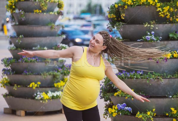 Feliz mulher grávida ao ar livre grande flor mãos Foto stock © vilevi