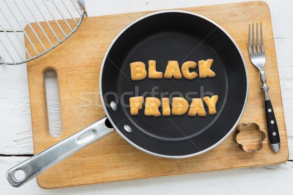 Cookie biscuits word BLACK FRIDAY in frying pan Stock photo © vinnstock