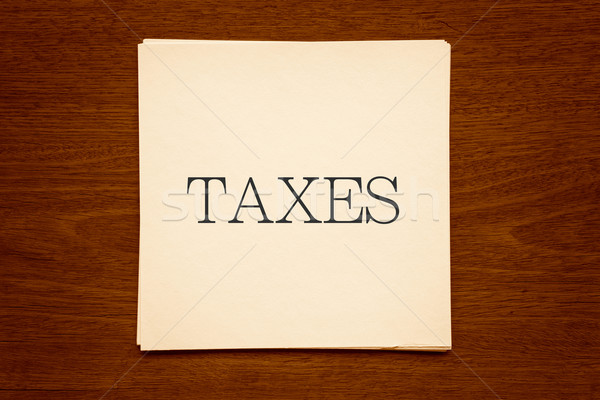 Paper cards with word ' TAXES ' on wood background in sepia Stock photo © vinnstock