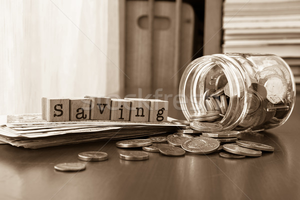Money saving word with coins and banknotes, Sepia toned Stock photo © vinnstock