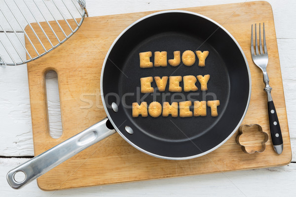 Alphabet crackers quote ENJOY EVERY MOMENT putting in pan Stock photo © vinnstock