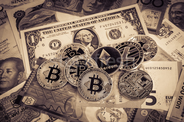 Cryptocurrency, bitcoins on foreign money, sepia vintage. Stock photo © vinnstock