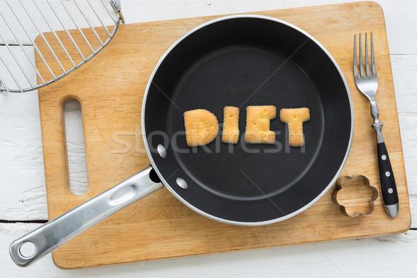 Alphabet crackers word DIET putting in pan Stock photo © vinnstock