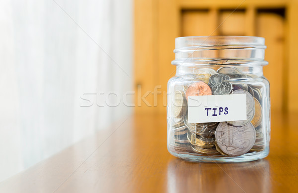 Stock photo: Glass bank for tips with money