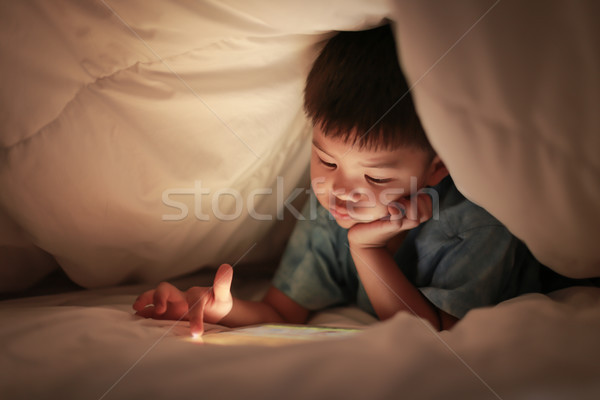 Kid play internet online game, under duvet. Stock photo © vinnstock