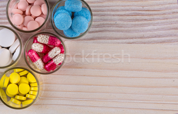 Various pills and capsules in glass containers top view Stock photo © viperfzk