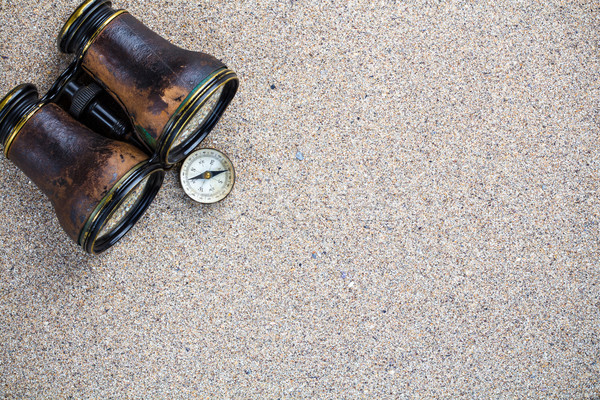 Sandy background with binocular and compass Stock photo © viperfzk