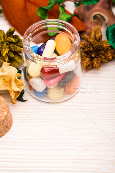 Various pills and capsules in glass container with green Stock photo © viperfzk