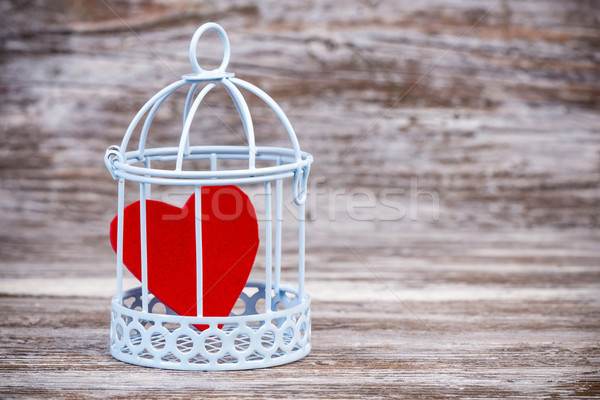 Heart in cage with wooden background Stock photo © viperfzk