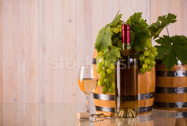 Bottle of wine with barrels grapes and grapeleaves Stock photo © viperfzk