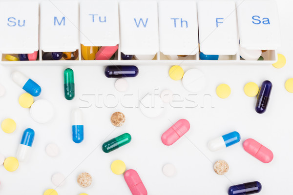 Color pills capsules and weekly pill organizer  Stock photo © viperfzk