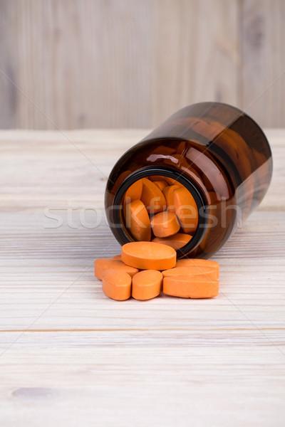 Narancs tabletták barna üveg konténer fa asztal Stock fotó © viperfzk