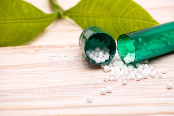 Nyitva kapszula kicsi fehér golyók zöld levél Stock fotó © viperfzk