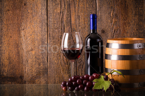 Glass of red wine with bottle barrel grapes on glass Stock photo © viperfzk