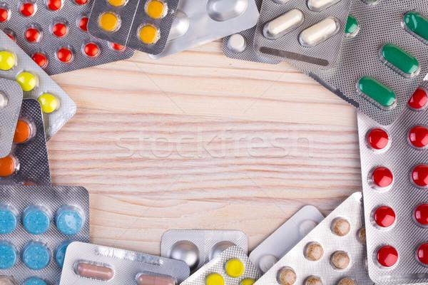 Pigułki kapsułki aluminium pojemnik drewniany stół medycznych Zdjęcia stock © viperfzk