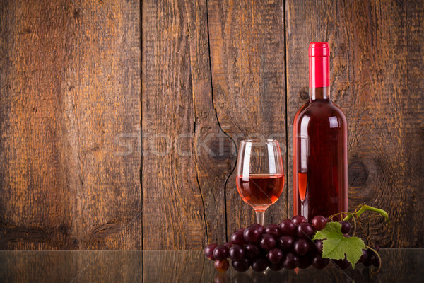 Stock photo: Glass of rose wine with grapes on glass