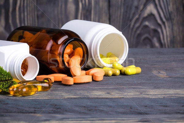 Various pills and containers with green leaves Stock photo © viperfzk