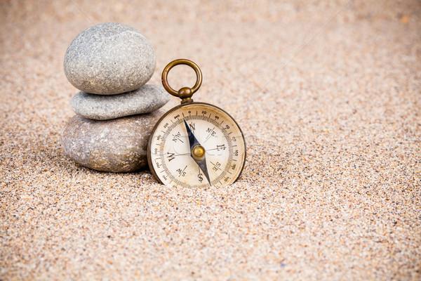 Klasszikus iránytű kavics kövek homok három Stock fotó © viperfzk