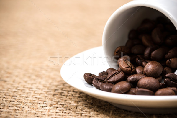 White coffeecup and plate with spilled coffeebeans Stock photo © viperfzk