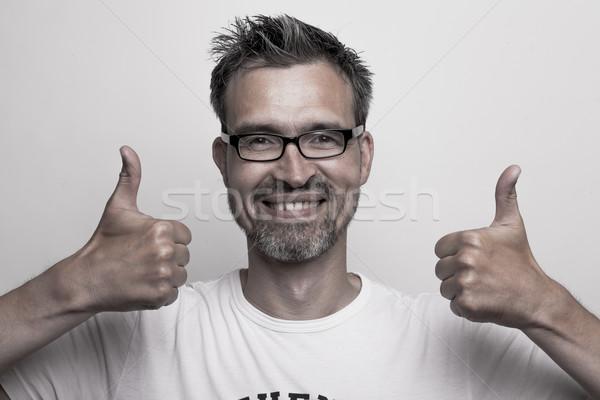 Smiling man holds his thumbs up Stock photo © vizualni