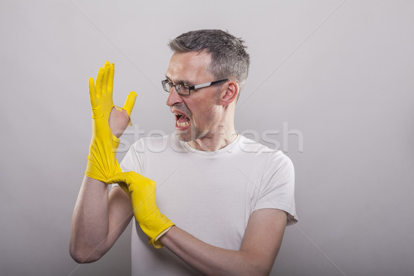 Man puts on yellow rubber gloves Stock photo © vizualni