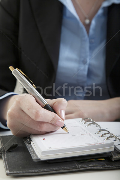 Stock photo: writing down a calendar entry