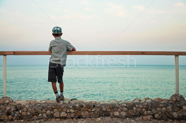 Stock photo: boy standing on quay in the dusk looking at sea
