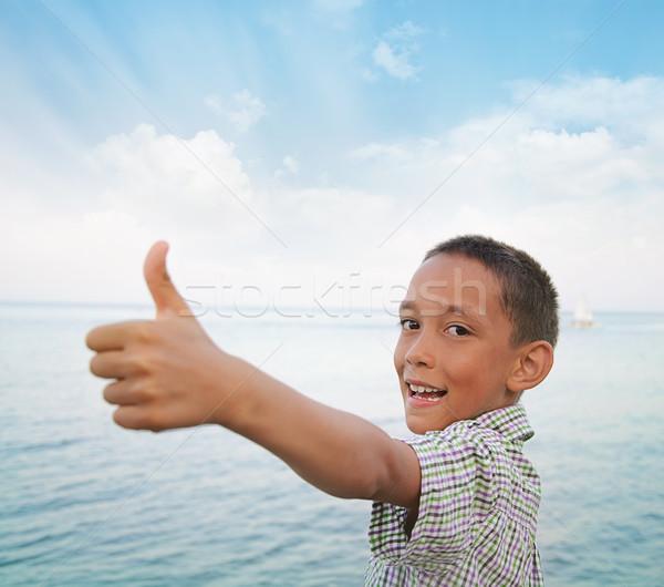 boy showing thumbs-up against sea Stock photo © vkraskouski