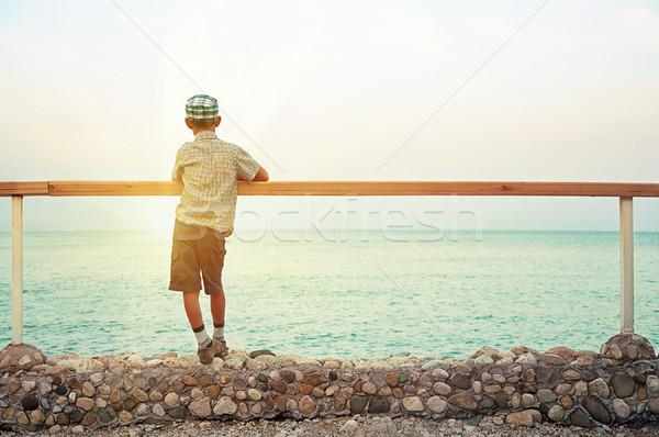 Fiú áll rakpart alkonyat néz tenger Stock fotó © vkraskouski