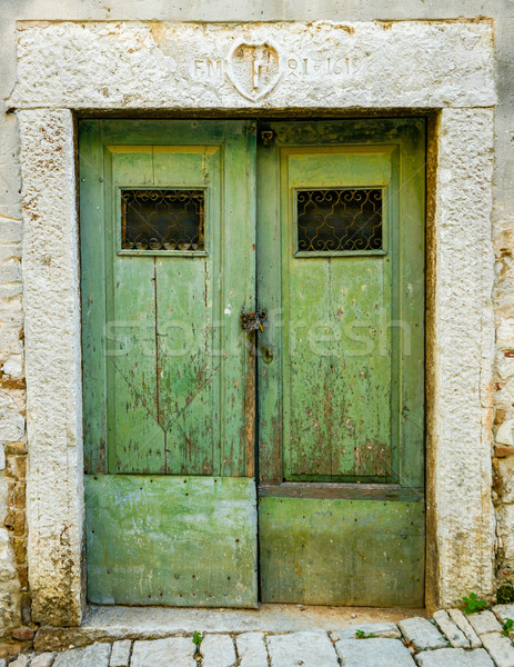 old green ragged shabby wooden door with wrought iron bars Stock photo © vlaru