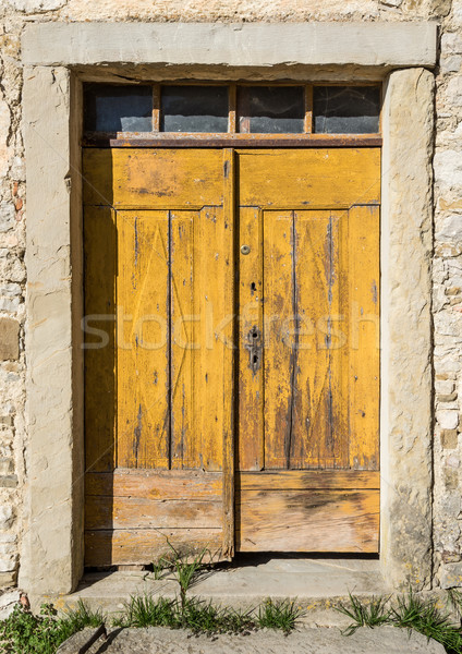 Stock photo: yellow ragged shabby wooden door
