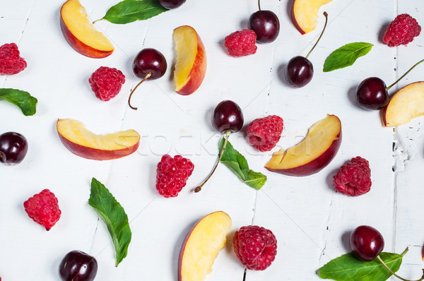 Various types of fruits with green leaves and frozen cocktail  berries on white wood background Stock photo © voloshin311