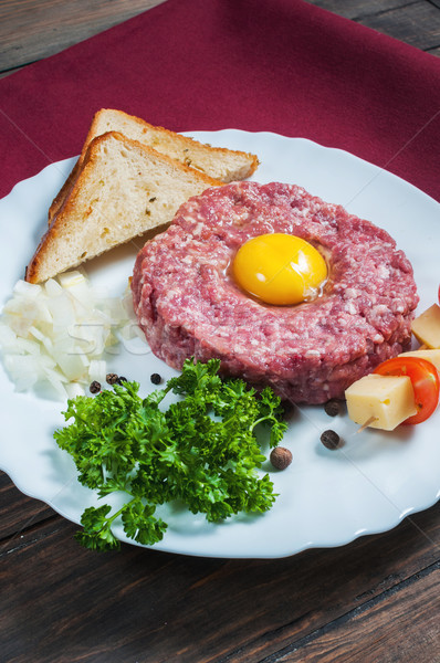 Beef tartare with bread and fresh onion on a wooden background. Stock photo © voloshin311