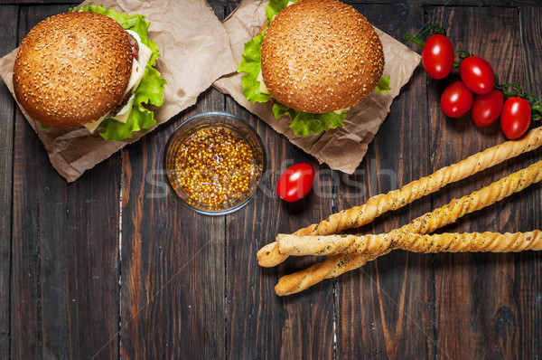 Stock photo: Fresh homemade burgers and breadsticks on wooden background