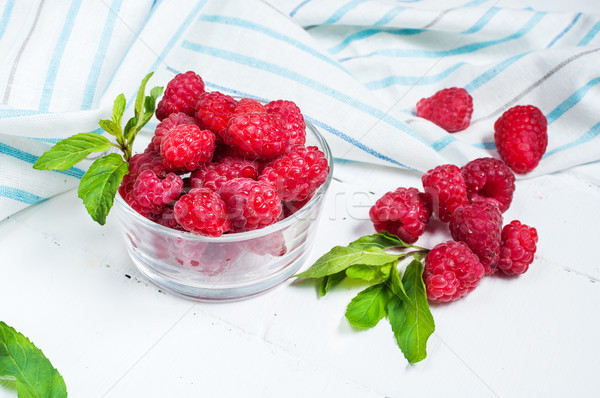 Ripe sweet raspberries in bowl on wooden table. Close up Stock photo © voloshin311