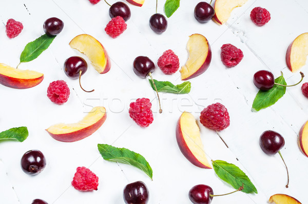 Various types of fruits with green leaves on white wood background Stock photo © voloshin311